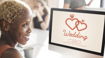 Woman sitting at computer viewing online wedding invitation