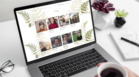 Hand holding coffee while looking at wedding party bios on wedding website
