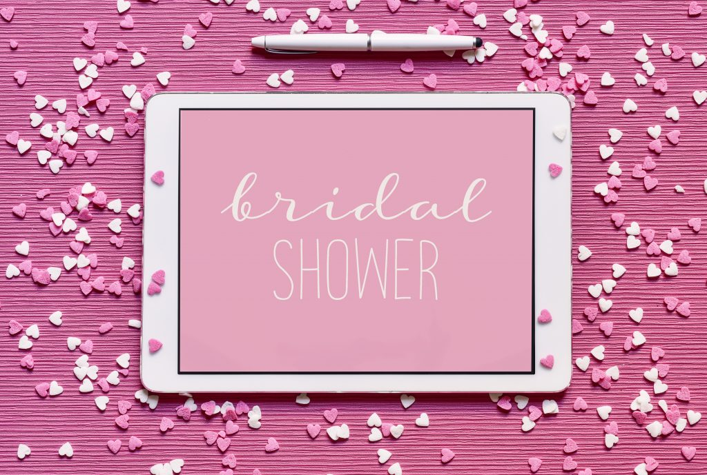 high-angle shot of a tablet with the text bridal shower written in white in it against a pink background, placed on a pink surface sprinkled with white and pink heart-shaped confetti sprinkles