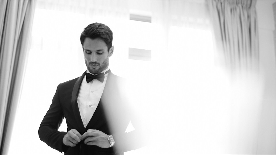 Black and white image of man buttoning suit for black tie preferred event.