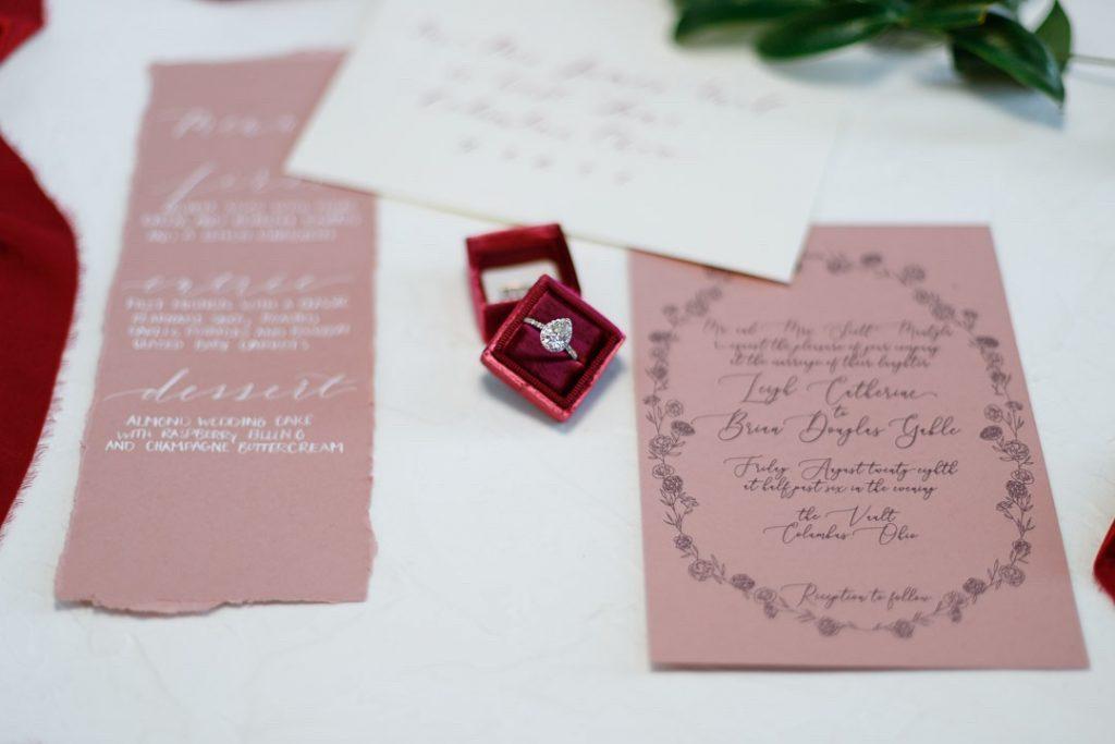 Wedding stationary suite surrounding red velvet ring case holding diamond engagement ring