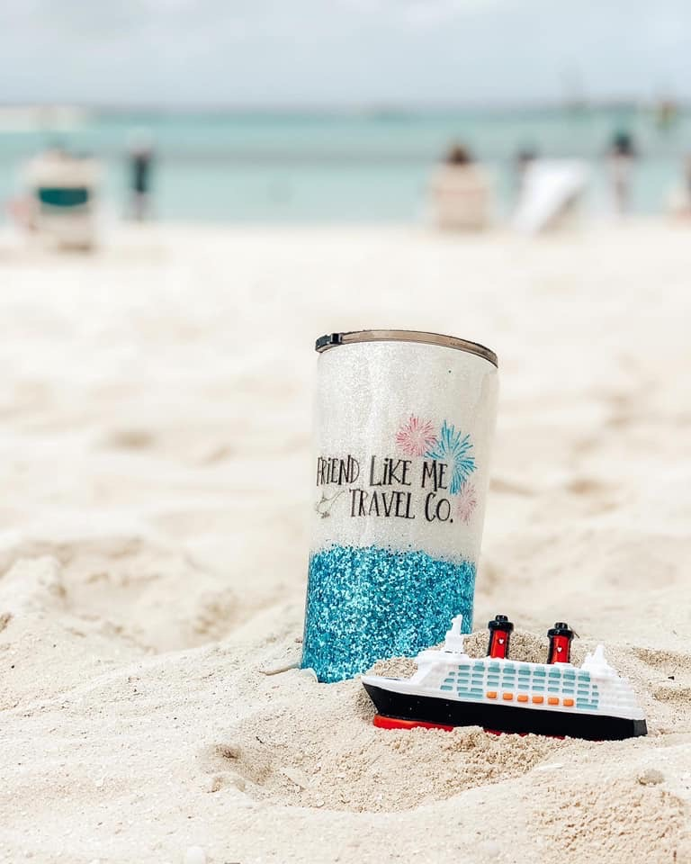 'Friend Like Me Travel Co' mug in the sand on a beach. Sitting next to Disney Cruise figure.