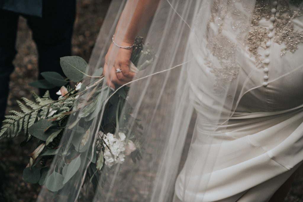 Bride wearing white wedding dress and holding flowers.