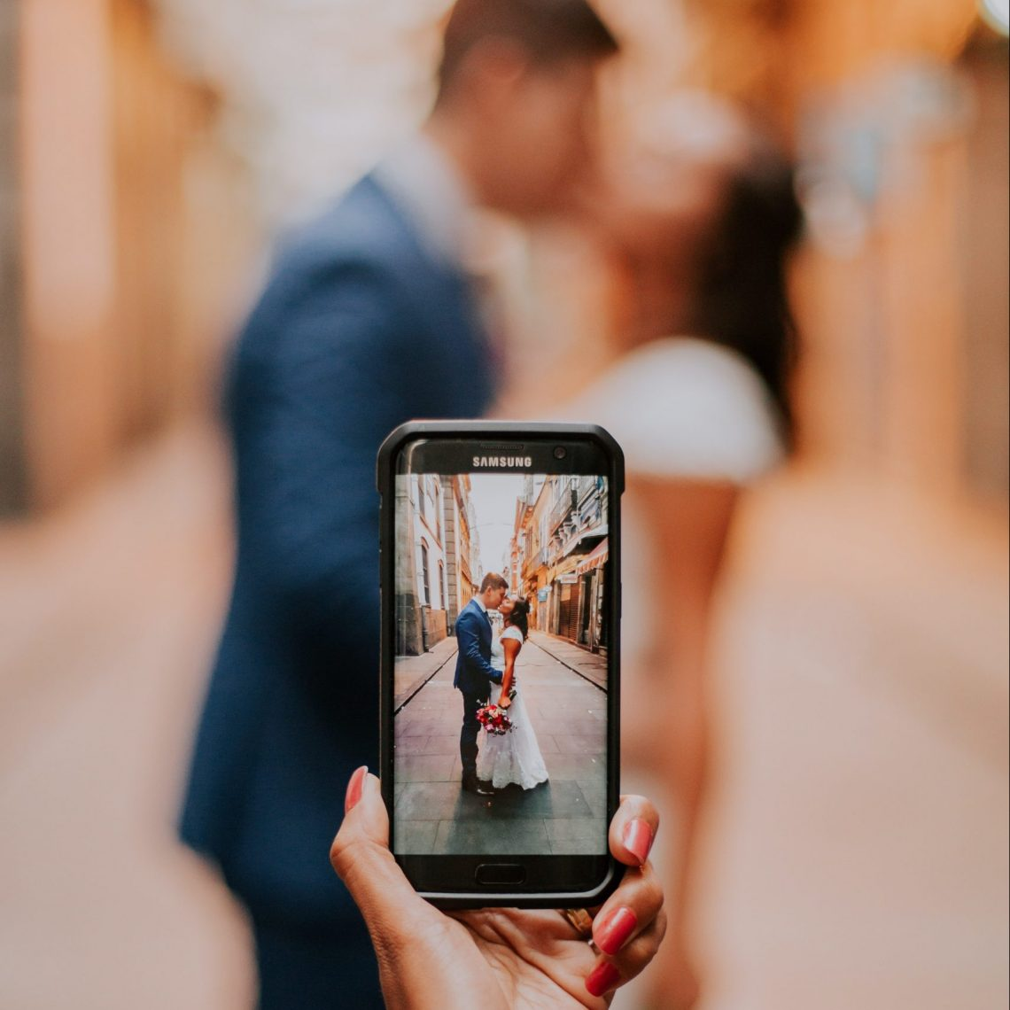 Hand holds phone in front of newly married couple