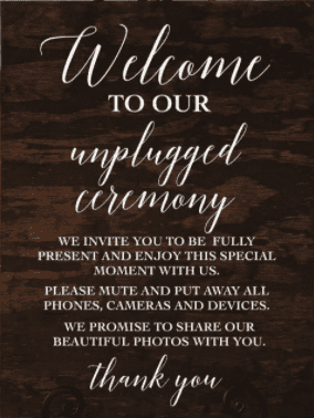 """Dark wooden wedding sign with white text. Sign reads """"welcome to our unplugged ceremony. We invite you to be fully present and enjoy this special moment with us""""."""