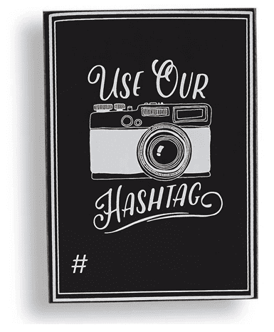 """Black chalkboard wedding sign with text """"use our hashtag"""" and an image of a camera. There is a blank space to write the hashtag."""