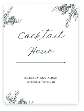 """White Wedding Sign with Greenery. Text states """"Cocktail Hour"""" with arrow pointing to the right."""