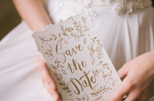 bride in white gown holding white and gold save the date for wedding